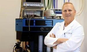 Dr. Hiatt standing in front of machine
