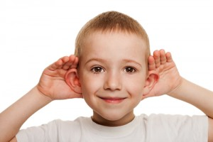 Male child with his hands on his his ears