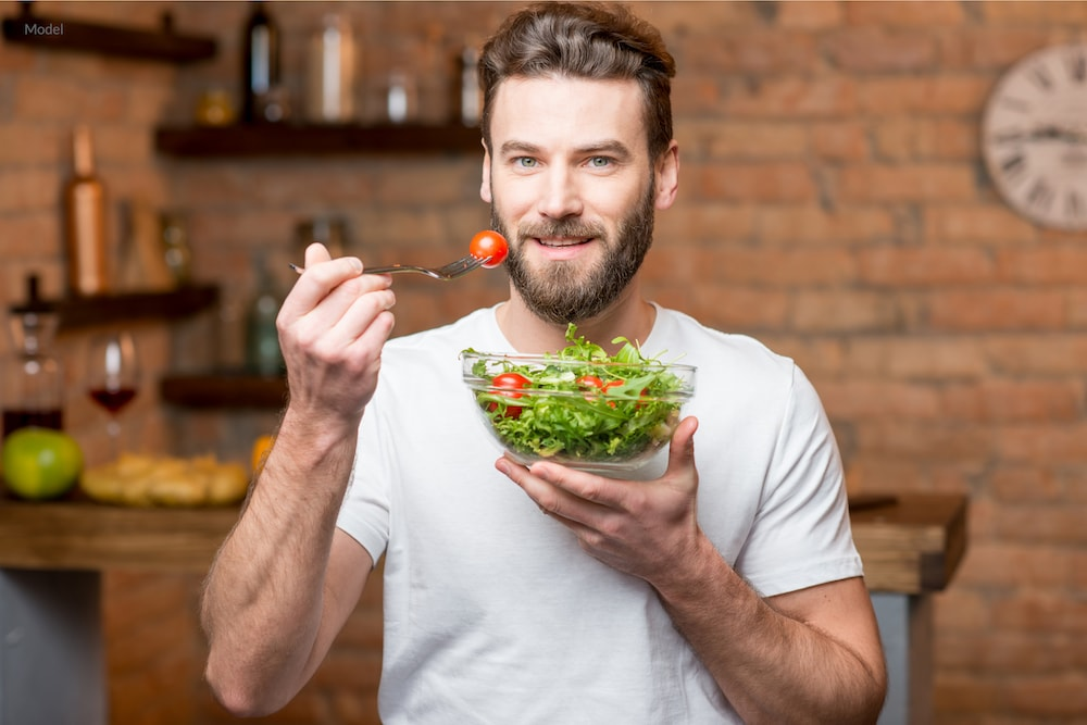 Healthy man eating a salad to maintain plastic surgery results.