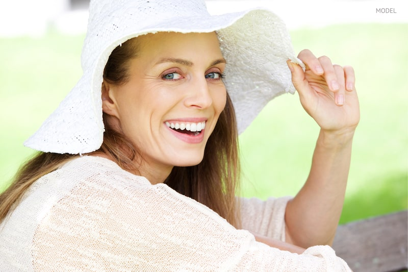 Beautiful middle-aged woman smiling and wearing a hat while outside.