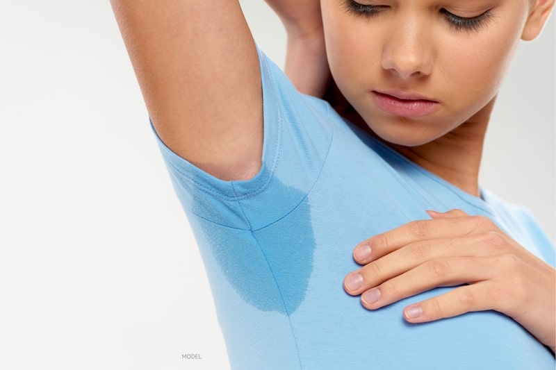 Woman dealing with very sweaty underarm.