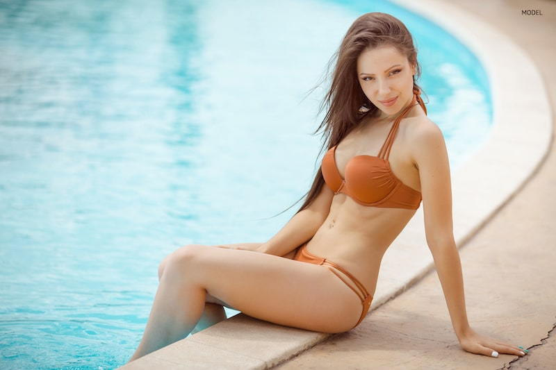 Young, fit woman sitting beside pool in burnt orange bikini.