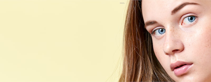 Close-up face of a teenage girl against a light yellow background.